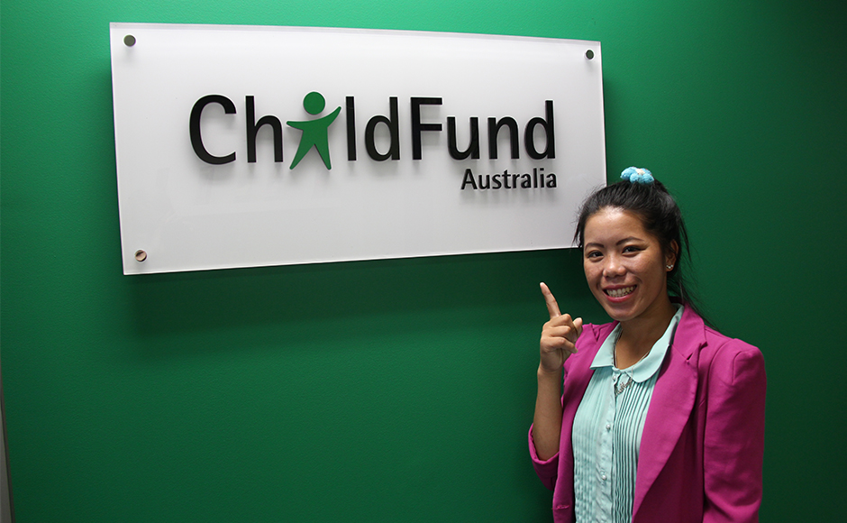 Lao Khang stands in front of ChildFund sign
