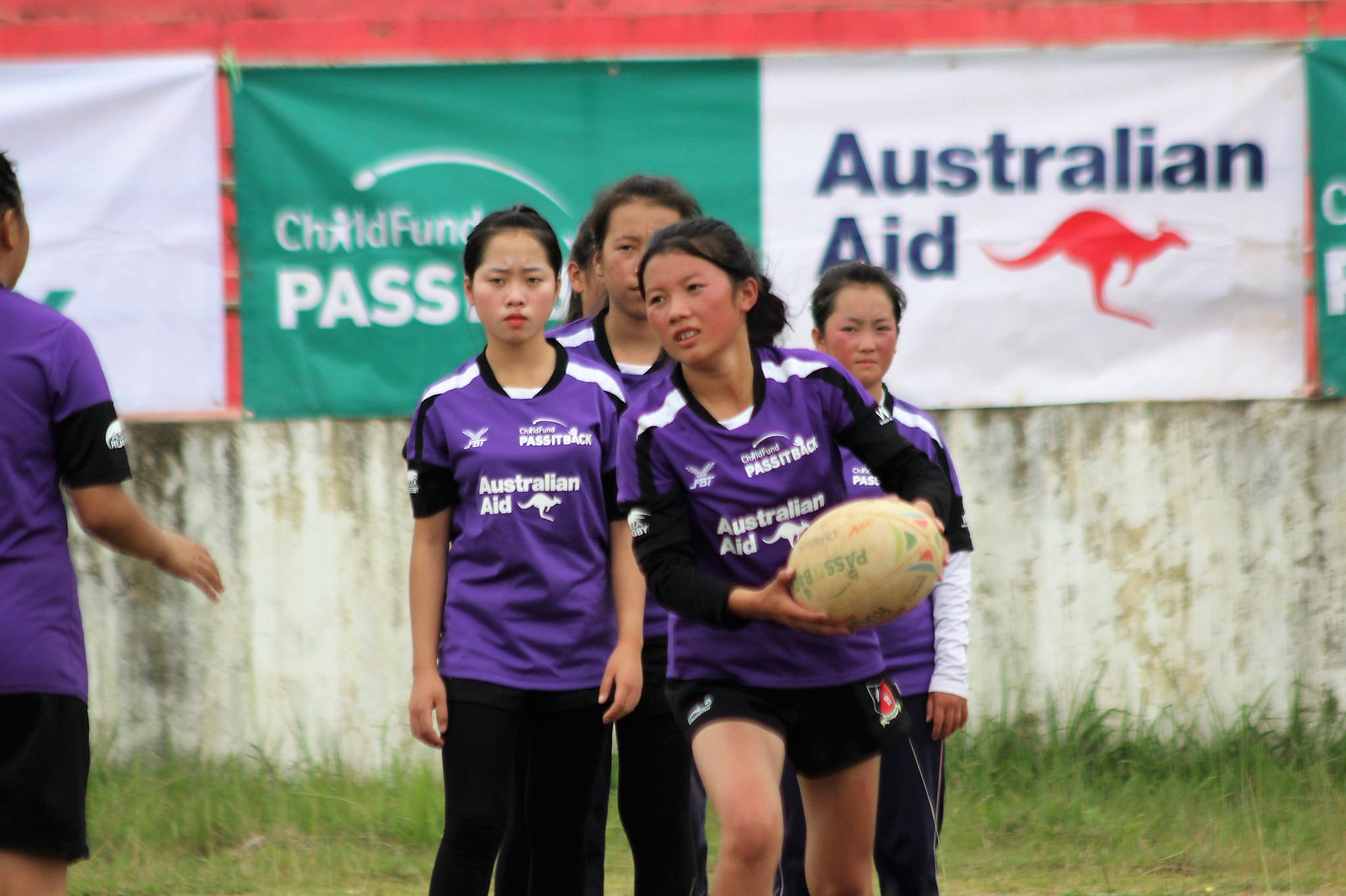 Lar runs with rugby ball while her team mates watch