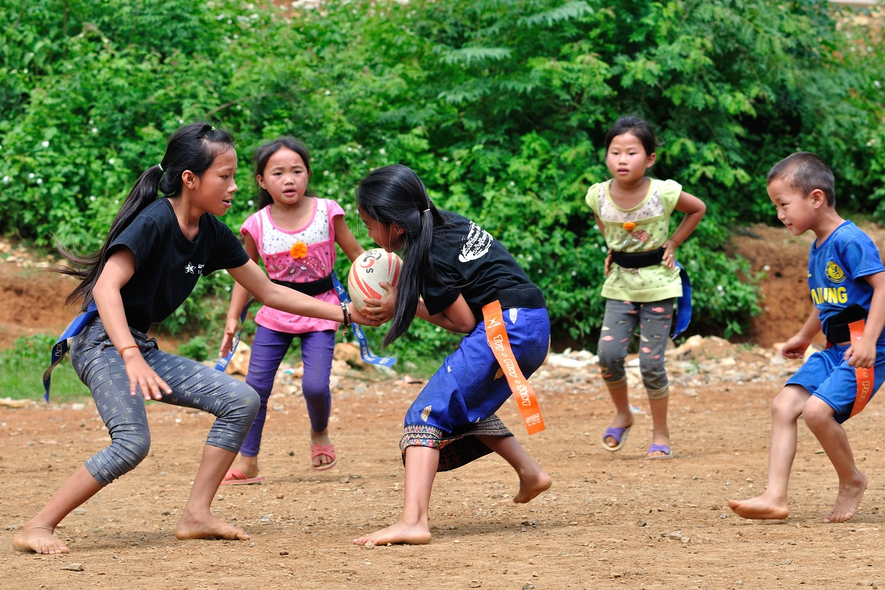 Young children in Laos play rugby in bare feet