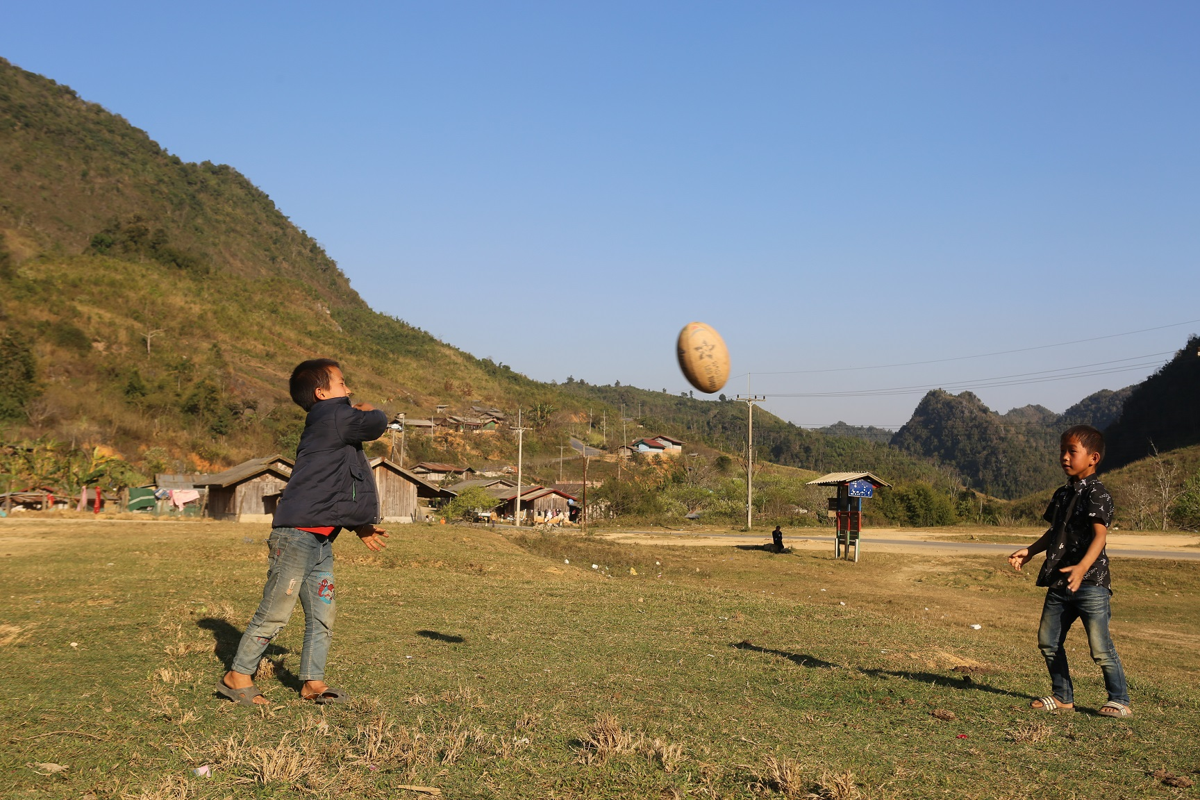 Two boys in a rural area throw a rugby ball to each other