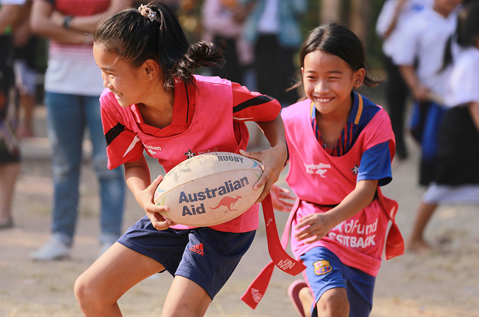 Girls wearing pink bibs playing rugby